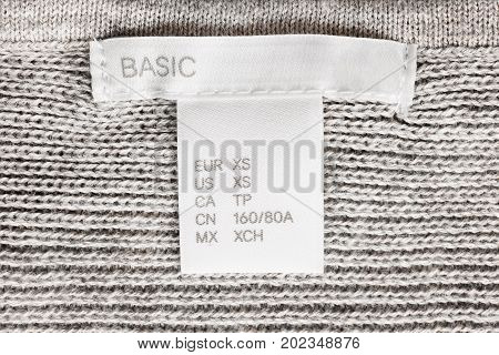XS size clothes label lettered basic on knitted background