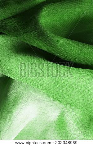 Draped green silk closeup as a background