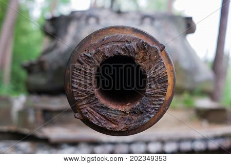 Old rusty barrel. Blurred tank in the background