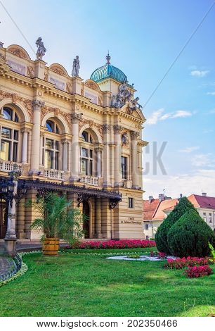 Krakow/Poland- August 15, 2017: part view of Juliusz Slowacki Theatre with cypress trees and flowers in a small garden near it, blue sky, summertime