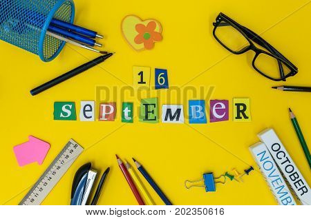 September 16th. Day 16 of month, Back to school concept. Calendar on teacher or student workplace background with school supplies on yellow table. Autumn time.