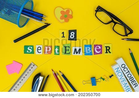 September 18th. Day 18 of month, Back to school concept. Calendar on teacher or student workplace background with school supplies on yellow table. Autumn time.