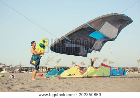 Professional man surfer carrying kite on the sandy beach in summertime