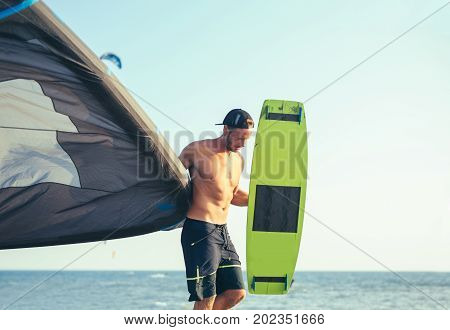Handsome Caucasian man professional surfer standing on the sandy beach with his kite and board.