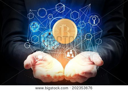 Businessman hands holding abstract bitcoin hologram on dark background. Cryptocurrency concept