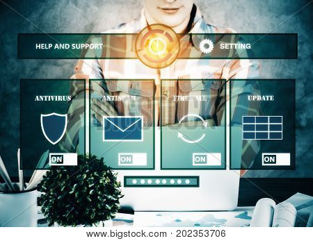 Unrecognizable young businessman sitting at workplace with abstract antivirus interface. Protection concept