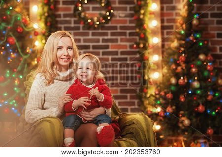 Merry Christmas and Happy Holidays! Cheerful mom and her cute daughter baby girl are smiling and having fun on christmas background. Parent and little child having fun near Christmas tree indoors.