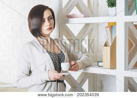 Portrait of thoughtful european woman drinking coffee or tea while standing in modern office with items on shelves. Morning breakfast break energy boost concept