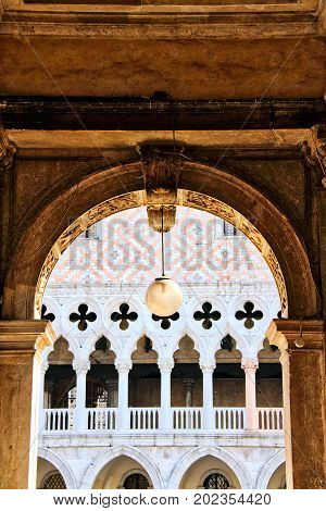 Detail of architecture in Piazza San Marco in Venice, Italy of an arch with a hanging light.