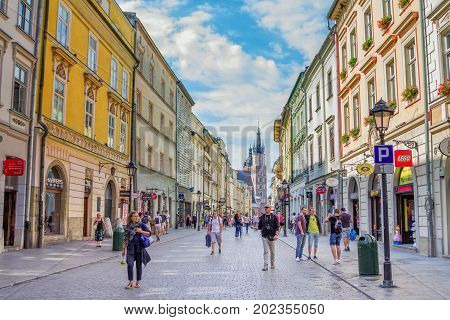Krakow/Poland- August 15, 2017: Cityscape of old town, tourists and citizens walking on Florianska street, view of town hall on background, sunny summer day with blue sky