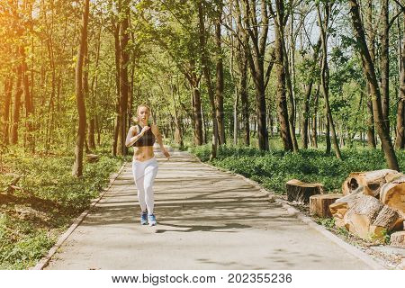 Woman Runner Running In Spring Lpark. Female Fitness Girl Jogging On Path In Amazing Fall Foliage La