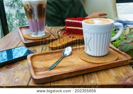Close Up. Hot Latte Coffee In White Mug With Spoon On Wooden Plate With Black Smart Phone And Sweet
