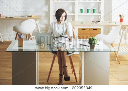 Busy business woman working on project at workplace. Female secretary using laptop and doing paperwork in modern office interior. Occupation concept