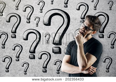 Thinking young caucasian man standing on concrete wall background with question marks. Curious confusion faq concept