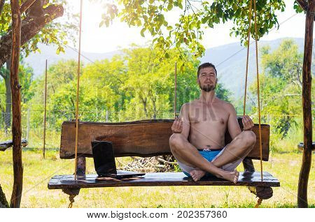 Businessman Relaxes After Working On Laptop Sitting In Lotus Pose Outdoors.