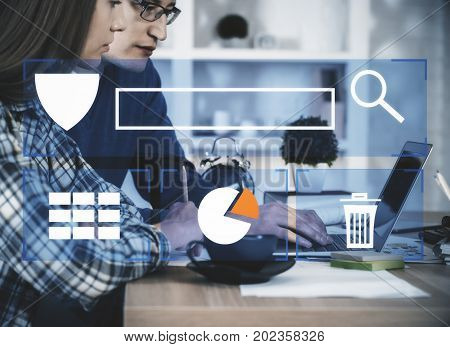 Side view of young businessman and woman using laptop together at workplace with digital antivirus touchscreen. Security concept