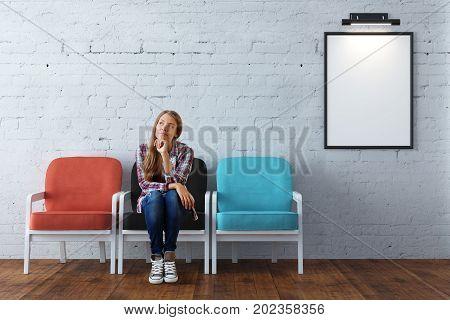 Thoughtful young woman sitting on chair in interior with white brick wall wooden floor and empty frame. Museum concept. Mock up 3D Rendering