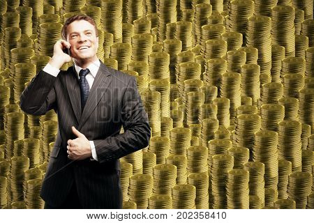 Handsome young businessman talking on the phone on abstract bitcoin pile background. E-commerce concept
