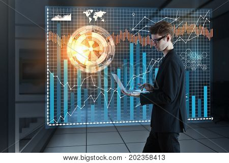 Side view of young businessman using laptop with abstract futuristic business projection on blurry interior background. Future and technology concept. 3D Rendering