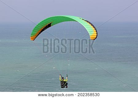 paraglider flying his wing above the sea
