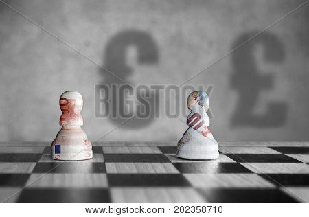 Chess pieces with euro verus pound currency symbol shadows in the background