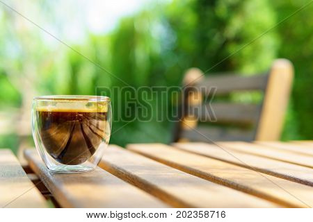 Espresso Coffee In Transparent Cup On The Wooden Table And Chair In The Garden. Coffee, Relax, Holid