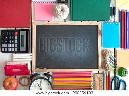 Top view of many stationery objects with blackboard in the centre