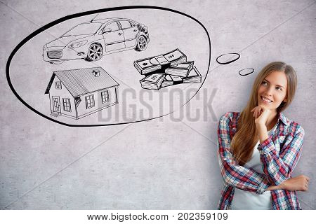 Attractive smiling young woman dreaming of wealth on concrete background. Rich concept