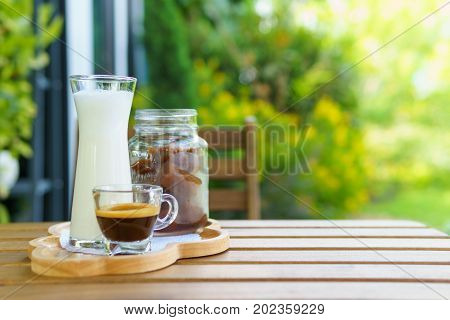 Iced Coffee Cube Latte With Milk And Shot Of Espresso On The Wooden Table In The Garden. Bright Tone