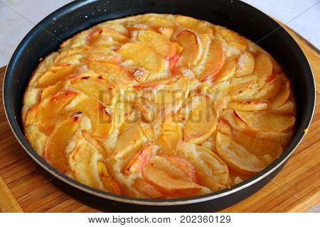 Baked charlotte with red apples in a baking dish