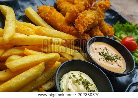fish and chips with salad cream and wasabi cream sauces in black ceramic dish on wooden table.