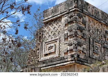 An image of an architectural detail of Puuc style in the very old Mayan city of Uxmal as background and background vegetation blue sky and clouds color. Yucatan. Mexico