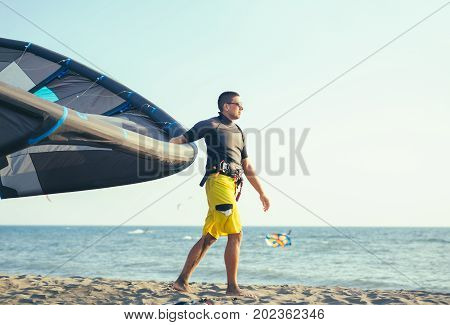 Handsome Caucasian man professional surfer standing in wetsuit on the sandy beach with his kite.