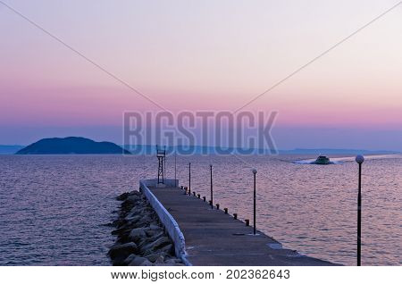 Pier at twilight with turtle island in a background, near the city of Neos Marmaros in Sithonia, Greece