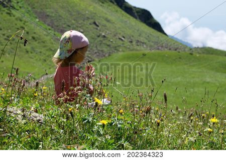 Little cute girl meditating in mountain landscape. Child meditating in lotus pose on the meadow, back view