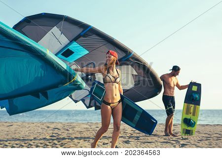 Pretty smiling Caucasian woman and man kitesurfer walking on the beach with their kite