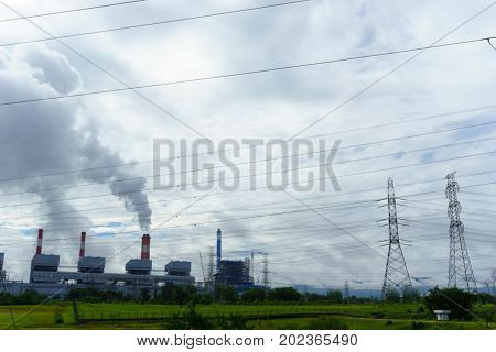 Coal Fire Power Plant Release Steam From Stack With Electrcity Transmission Line And Cloudy Sky.