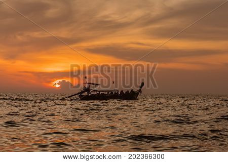 Traditional thai longtail boat at sunset beach. Ao Nang, Krabi province.