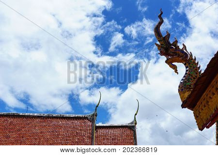 Statue Of The Head Of The Serpent On The Corner Of Roof And Red Roof With Blue Sky And Cloud