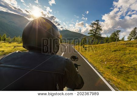Detail of motorcycle driver. View from co-driver perspective, beautiful Alpine landscape in sunset light. Travel and sport photography in outdoor. Speed and freedom concept