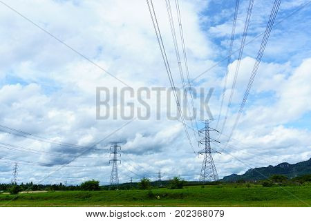 High Voltage Electricity Pylon And Transmission Line In The Field With Blue Sky And Cloud