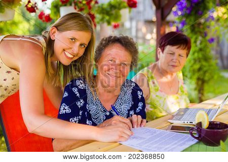 Portrait with smiling daughter while her elderly mother is signing succession testament for she.