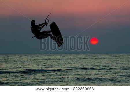 Kite boarding. Kitesurf freestyle at sunset. Acrobatic