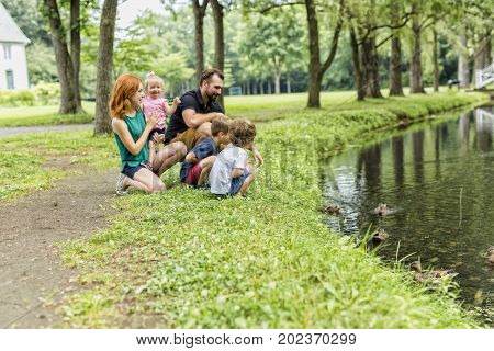 A Families with children close to a waterscape with duck on it