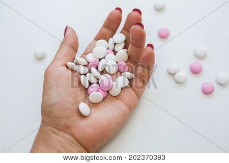 Depressed girl with pills in hand over grey