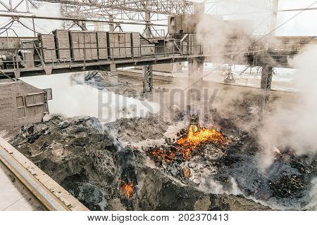 Electrical overhead crane with mechanical multivalve clamshell grapple over evaporation of molten liquid red-hot iron and slag in slag dump. Metallurgical heavy industry.