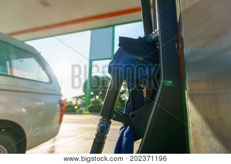 car waiting for fill fuel with petrol pump nozzle at gas station in sunny day before gas price is up tomorrow.