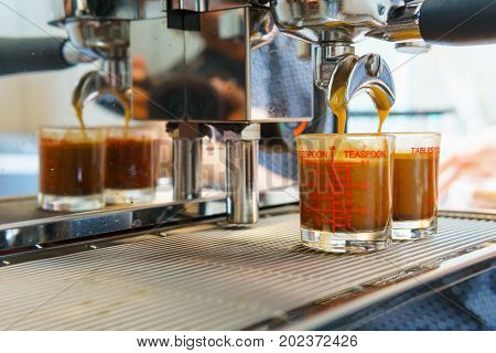 Close up of espresso coffee pouring from coffee maker machine to glass shot. barista coffee brewing concept.