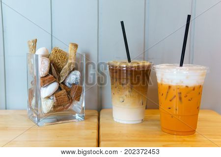 Close Up Of Iced Latte Coffee And Thai Tea In Transparent Plastic Glass And Straw On The Wooden Tabl