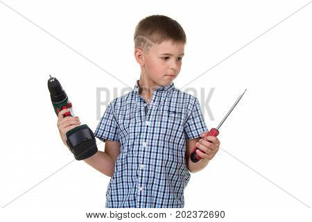 Little thoughtful boy builder in checkered shirt holds a drill and a screwdriver in his hands, isolated on white background